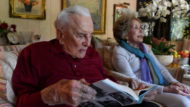 Film legend Kirk Douglas, left, peruses the new book he authored with his wife, Anne, who is seated next to him.