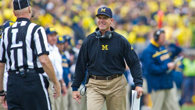 Michigan head coach Jim Harbaugh confronts a line judge on the sideline in the fourth quarter of an NCAA college football game against Oregon State in Ann Arbor, Mich., Saturday, Sept. 12, 2015. Michigan won 35-7.