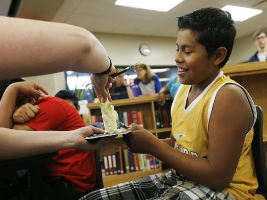 Gilmer Mejia Solano, 11, helps Sarah Pratt, the sculptor of the Iowa State Fair Butter Cow, carve an ear of corn out of a stick of butter June 25, 2015, as Pratt helps kick off a state fair-themed language fair during an English Language Learners summer school program at Meredith Middle School in Des Moines.