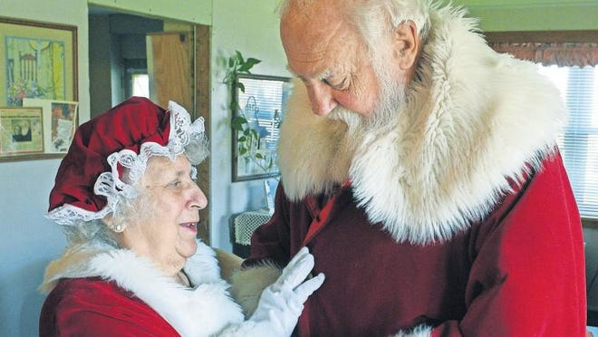 Elaine Rogers, dressed as Mrs. Claus, straightens her husband Santa Stan's suit before an event last year. Rogers is preparing for his season as Santa Claus at the Mall of Monroe beginning Saturday. [MONROE NEWS FILE PHOTO BY TOM HAWLEY