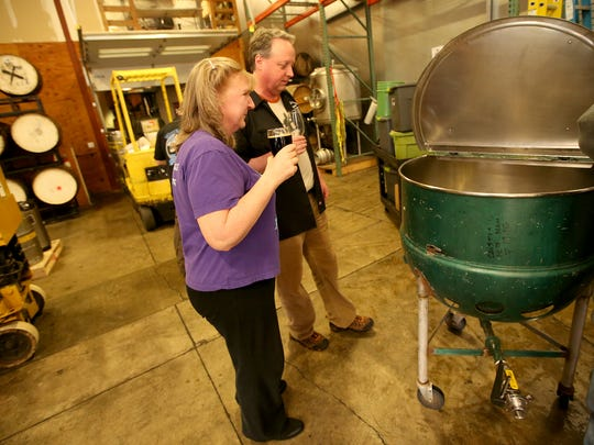 Marti Gwaltney and Alan Moum look over a piece of the original brewing equipment used by the club founder Don Spencer.