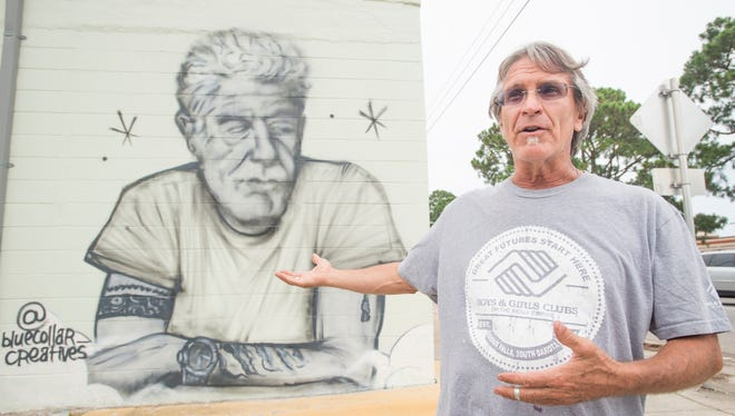 Owner Ric Kindle talks about the Anthony Bourdain mural that is painted outside of his new Live Juice Bar that is under construction in downtown Pensacola on Monday, June 18, 2018.  Kindle and the artists want to bring awareness to suicide prevention.