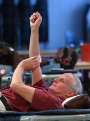 Bill Benton applies pressure to his arm after donating blood.