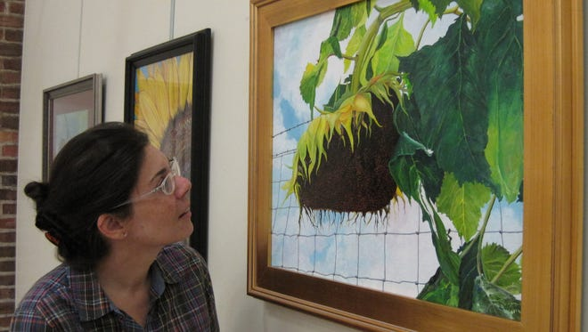 "Exhibition Juror Amanda Karioth Thompson, Education and Exhibition Director with COCA, is enamored with ""Faded Sunflower"" by Robert DeWitt Smith, art instructor at the Senior Center. The painting will be awarded 1st place at the reception for the 9th Annual Senior Artist Showcase on Friday, Sept. 2, from 6-8 p.m., Tallahassee Senior Center, 1400 N. Monroe St."