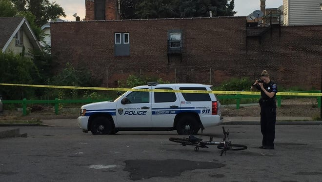 A Rochester police technician photographs a bicycle at the scene of a shooting in front of 857 Portland Ave.