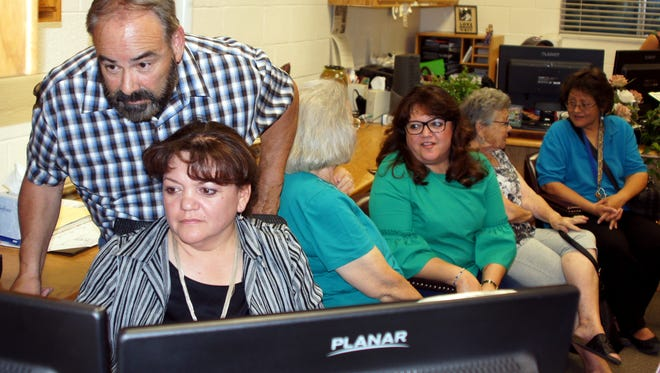 In the foreground, Michelle Martinez Holguin spent some tense moments in front of a computer monitor Tuesday night as the Luna County Primary Election results streamed in. Looking on is her husband Ernie Holguin fro the Luna County Treasurer's Office. Martinez Holguin outdistanced her Democratic challenger Chris Jasso by garnering 72 percent of the vote for the Luna County Assessor's post. Martinez Holguin will run unopposed in the November General Election.