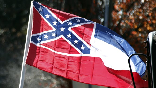 A Mississippi state flag is unfurled by Sons of Confederate Veterans and other groups on the grounds of the state Capitol in Jackson in January 2016 in support of keeping the Confederate battle emblem on the state flag.