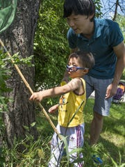 Jae Yeong Heo watches the technique his son, Juin Heo, 3, uses to catch insects during the Insect Safari with Dad on Sunday at Legg Park.