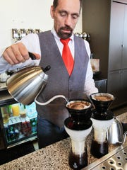 Chuck Downey creates a poured over coffee iced drink for a customer at Hubbard & Cravens in Carmel City Center.