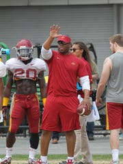 Cyclone running backs coach Lou Ayeni instructs his