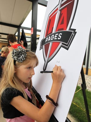 Chloe Studincki signs her name on the poster board with its new logo for Seton Elementary as the Unified Catholic Schools of Oshkosh reorganize under the new name of Lourdes Academy during its unveiling at the Lourdes High and Middle school building Aug. 8, 2012.