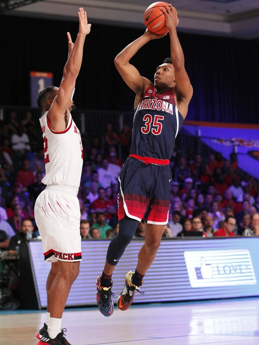 In this photo provided by Bahamas Visual Services, Arizona guard Allonzo Trier (35) shoots over North Carolina State guard Allerik Freeman (12) during an NCAA college basketball game, Wednesday, Nov. 22, 2017, in the Battle 4 Atlantis tournament in Paradise Island, Bahamas. N.C. State defeated Arizona 90-84. (Tim Aylen/Bahamas Visual Services via AP)