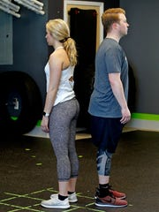 Courtney Tarmann and Nathan Kowalczyk demonstrate the starting position for the partner wall sit exercises at bodyfuel inc.