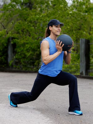 Catherine Andersen, owner and coach from Achieve Personal Fitness and Milwaukee Adventure Boot Camp, shows the starting position for the medicine ball lunge with overhead press exercise.