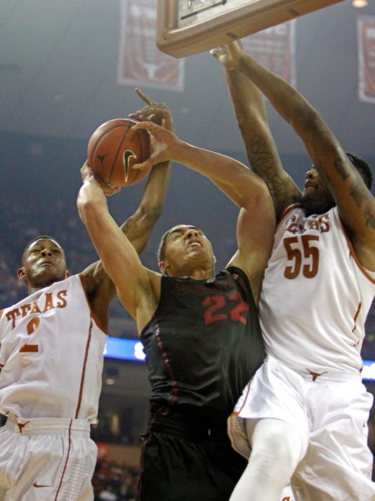 Stanford forward Reid Travis (22) goes to the basket against Texas guard Demarcus Holland (2) and Cameron Ridley (55) during the first half of an NCAA college basketball game, Tuesday, Dec. 23, 2014, in Austin, Texas. (AP Photo/Michael Thomas)
