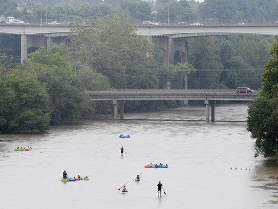 People float down the French Broad River through the River Arts District in July 2017.