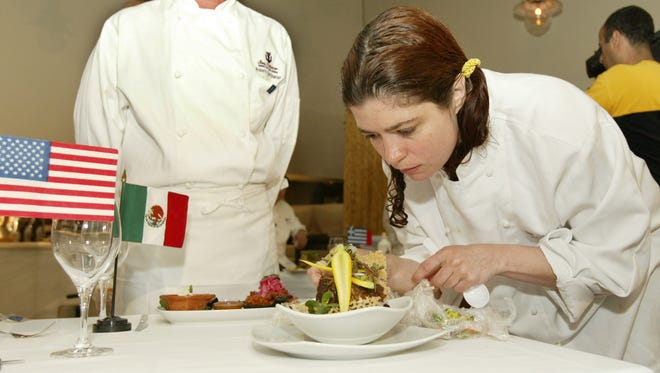 Rosa Mexicano culinary director Roberto Santibanez, left, looks on as chef Alex Guarnaschelli constructs her dish prior to a tasting by New York Mayor Michael Bloomberg at Milo's Estatorio restaurant in New York on June 17, 2004. Guarnaschelli, a regular on Food Network?s Chopped and Iron Chef America and author of ?Old School Comfort Food?, said home cooks have started looking for new sources to heighten flavors.