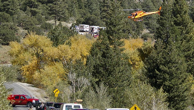 A Flight for Life Helicopter rises above backed up traffic Monday Sept. 30, 2013,  in south-central Colorado.  Roads were closed as emergency personnel work to  aid hikers trapped after a rock slide on the trail to Agnes Vaille Falls.