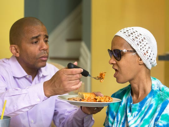 Christopher feeds dinner to Pamela. She can no longer feed herself. Most meals are brought in by friends and family.