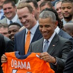 President Barack Obama holds up a Denver Broncos team football jersey as he welcomes the Super Bowl Champions during a ceremony in the Rose Garden of the White House in Washington, Monday, June 6, 2016, to honor the team and their Super Bowl 50 victory. Standing behind Obama is Peyton Manning.