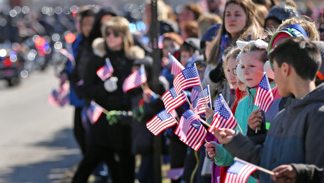 Students and school staff watch the funeral procession of Boone County Deputy Jacob Pickett pass the White Lick Elementary School in Brownsburg, Friday, March 9, 2018.