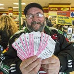 Robert Charbonneau of Saint-Donat, Quebec, holds up $1,000 in Powerball tickets in Champlain, N.Y.