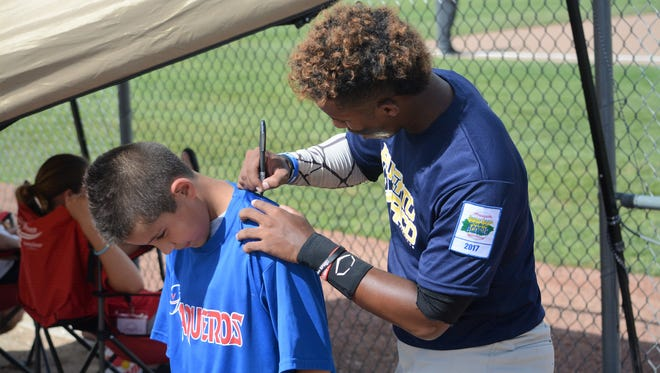 A young Vaqueros fan gets an autograph on the back of his shirt Sunday at Farmington Sports Complex. The Vaqueros traveled from Puerto Rico for the Connie Mack World Series.