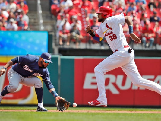 Milwaukee Brewers second baseman Jonathan Villar, left, handles a ground out by St. Louis Cardinals' Kolten Wong as Cardinals' Jose Martinez, right, heads safely to second during the second inning of a baseball game Wednesday, April 11, 2018, in St. Louis. (AP Photo/Jeff Roberson)