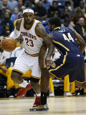 Cleveland Cavaliers forward LeBron James (23) dribbles the ball past Indiana Pacers forward Solomon Hill (44) during their preseason game at the Cintas Center on Xavier University campus.