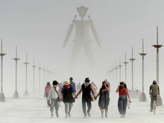 Burning Man participants walk through dust at the annual Burning Man event on the Black Rock Desert of Gerlach, Nev., on Friday, Aug. 29, 2014.