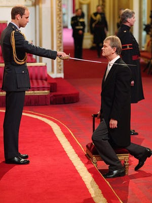Prince William hosts his first honors ceremony, bestowing knighthoods with ceremonial sword, in this picture headteacher Sir Kenneth Gibson, at Buckingham Palace on Oct. 17.