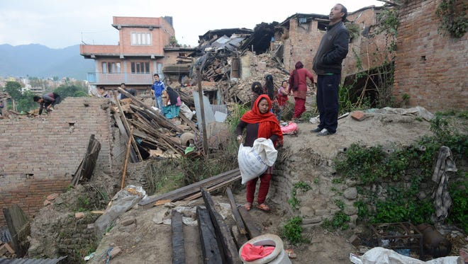 People carry their belongings amid the rubble of collapsed houses in Bhaktapur, on the outskirts of Katmandu, on April 27, two days after a magnitude-7.8 earthquake hit Nepal.