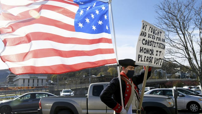 Andrew Brown, 16, dressed as a Colonial soldier, stands with an American flag and a sign urging residents to vote outside a polling station at the St. Elizabeth of Hungary Parish Center in North Adams, Mass. on Tuesday, Nov. 3, 2020. Brown, a history buff, said that he wishes he was old enough to vote.