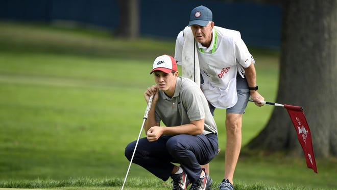 Davis Thompson looks over the eighth green with his father and caddie Todd Thompson during the first round of the U.S. Open golf tournament at Winged Foot Golf Club