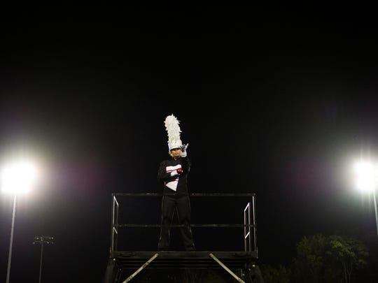 Halls High's drum major drops an apple as part of the opening salute during the Knox County Band Exhibition held at Farragut High School Thursday, Oct. 5, 2017.