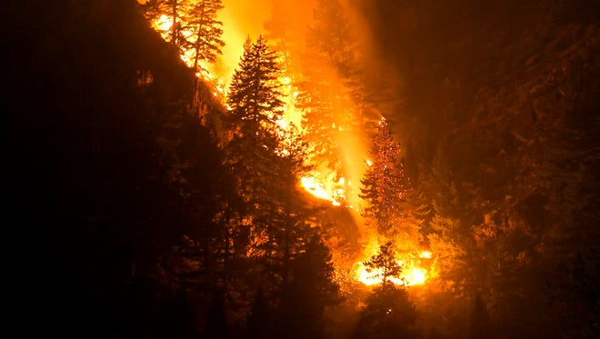 Fire creeps slowing down the western canyon wall above the Wood River in Hailey where firefighters continue to battle the Beaver Creek Fire Saturday Aug. 17, 2013. (AP Photo/Idaho Statesman, Darin Oswald) ORG XMIT: IDBOI101