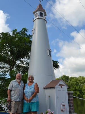 Bob Severs and Viola Purdy stand next to the 27-foot lighthouse Severs built on the dock across from their home on the Sandusky River. The lighthouse is made primarily of scrap aluminum from a Boeing 747.