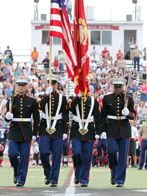 A Marine Corps color guard takes the field before the start of the 2013 Basilone Bowl, a high school football all-star game.