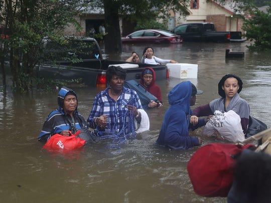 People walk down a flooded street as they evacuate