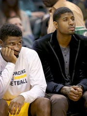 Indiana Pacers forward Paul George (13), right, sits on the bench with Solomon Hill, left, in the second half of their game Saturday, March 14, 2015, evening at Bankers Life Fieldhouse. The Pacers lost to the Celtics 89-93.
