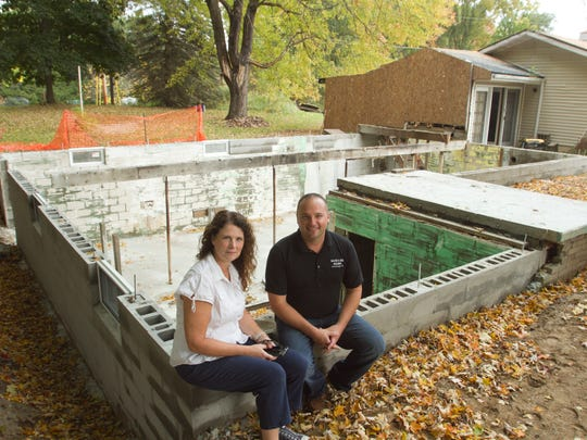 """Unadilla Township trustee Sue Cox sits on the foundation of the home she has now been given the green light by architects to rebuild after a fire reduced it to rubble. With Cox is Mike Dalton of Dalton & Zick Builders. Cox says of Dalton, """"He is my saint,"""" for working so diligently to put the house up again."""