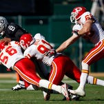 Linebacker Derrick Johnson (56) and defensive ends Tamba Hali (91) and Jared Allen of the Chiefs bring down quarterback Duante Culpepper of the Oakland Raiders in a 2007 game.
