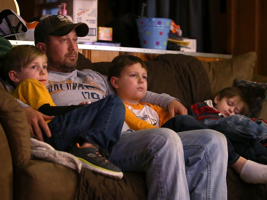 Lynn Fortner sits with his sons 6-year-old Lucas, left, 8-year-old Trey and 2-year-old Christian at their home in Trenton, Tenn., on Friday, Dec. 9, 2016.