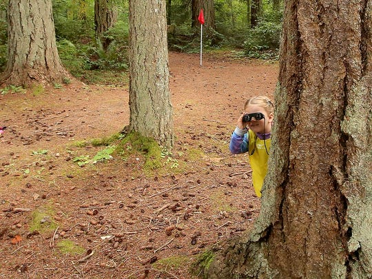 A camper hides behind a big tree and uses her binoculars during the Magnolia Forest Preschool camp at Kitsap Memorial Park in Poulsbo on Tuesday.