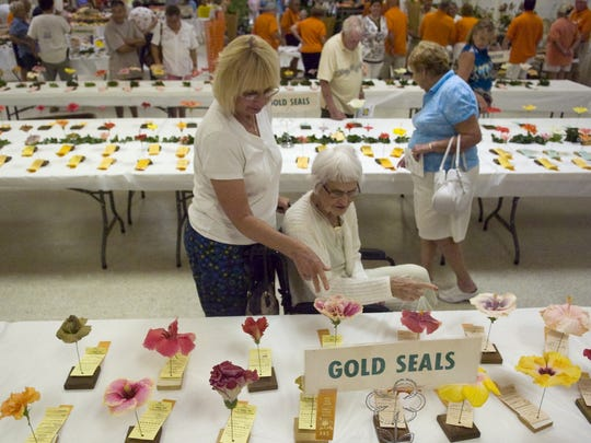 Kay Cunningham, left, of Cape Coral and her mother, Pat Fracke of Fort Myers browse a previous Hibiscus Show at the Araba Shriners Center in Fort Myers. The show, run by the James E. Hendry Chapter of the American Hibiscus Society, features a large display of blooms from plants grown by society members on display and plants for sale.