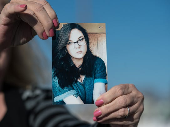 Margret Wood holds a photo of her daughter, Sarah,