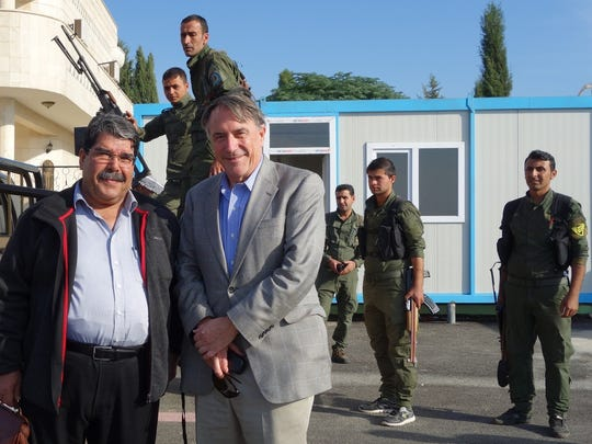Peter Galbraith, center, poses with Saleh Muslim, president of the Syrian Kurdish party PYD, in Qamishli, Syria.