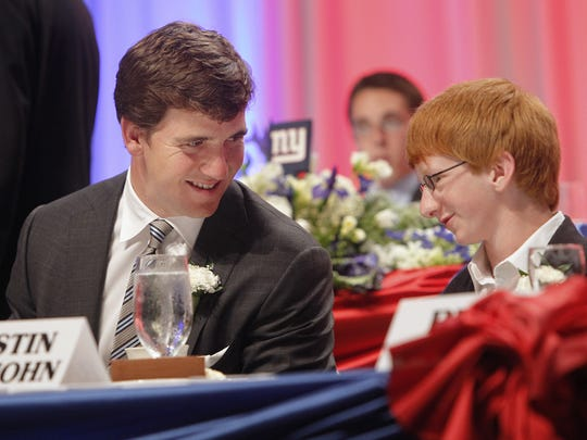 Eli Manning, left, shares a moment with honorary dinner