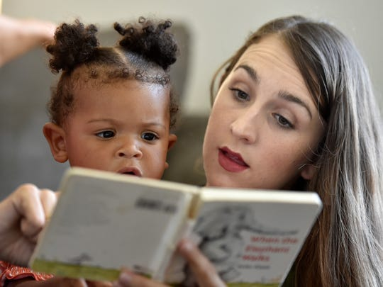 "Allysha Drew (right) reads from ""When the Elephant Walks"" with daughter, Madelyn, 11 months, during family time Aug. 3, 2017, in their home at Patrick Air Force Base in Cocoa Beach."