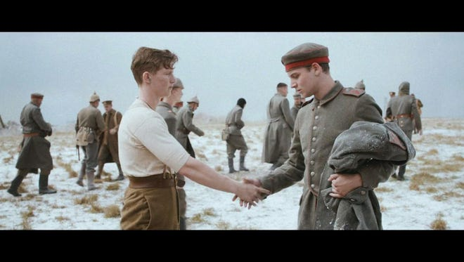An actor dressed as a German WWI soldier, right, and an actor dressed as a British WWI soldier left, shake hands.